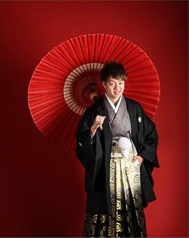 朱色の傘を持った袴姿の成年